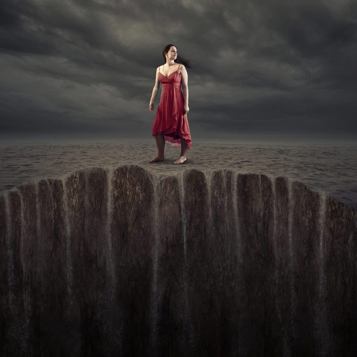 A woman standing on sand that is sinking.
