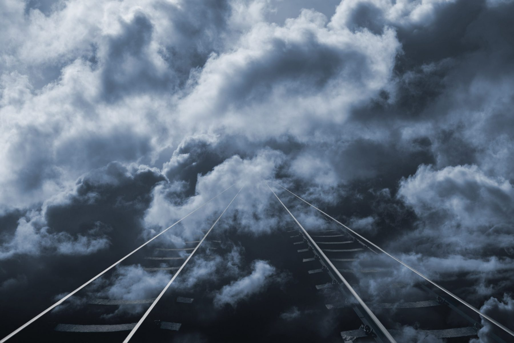 Train tracks stretching into distant cloud.