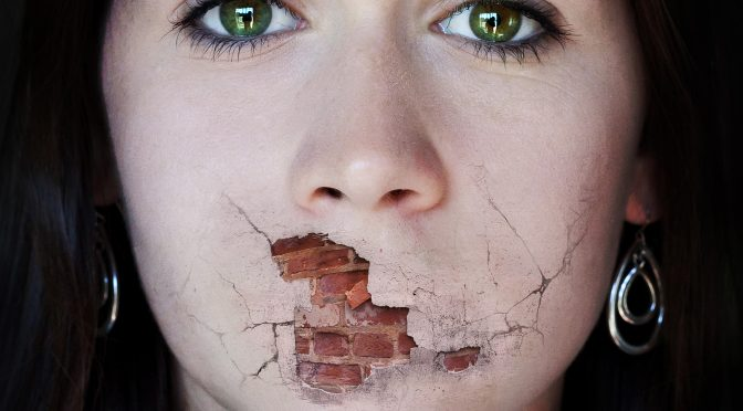 A woman tries to speak but her mouth is a broken brick wall.